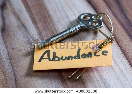concept for a happy abundant life using an old decorative key and a hand written tag attached by a golden cord