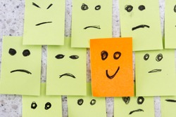 concept for a positive attitude with small office notes with multiple faces and one that stands out with a smile