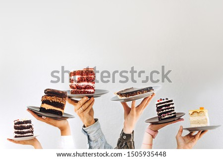 Concept for cafe or bakery with desserts: plates with different cakes in people's hands, place for your text Сток-фото ©