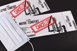 Concept for cancelled entertainment events during Corona virus pandemic with concert tickets and red 'cancelled' stamp on them and face mask