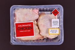 Concept for chlorinated chicken with pack of raw chicken thighs with warning label