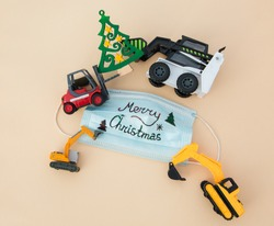 concept for Christmas business greetings at construction company amid covid-19 pandemic. multi-colored toy models of forklift, excavators, loader around medical mask with wish for merry christmas.