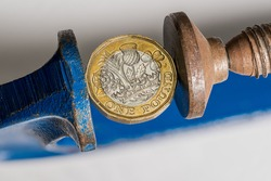 Concept for financial stress or recession with UK one pound sterling coin being squeezed between the jaws of a large vise. Detailed macro shot of vice