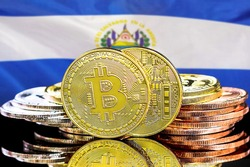 Concept for investors in cryptocurrency and Blockchain technology in El Salvador. Bitcoins on the background of the El Salvador flag
