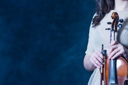 Concept for music news. Copy space. Smoky background. Close-up. Violin and bow in female hands.