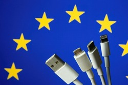 Concept for new EU legislation on USB-C universal charging cable. EUROPEAN UNION flag and different charging cables such as USB, USB-C, Micro USB, lightning cable.
