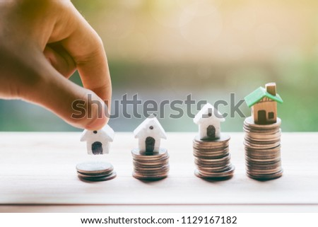 Concept for property ladder, mortgage and real estate investment. Man's hand putting house model on top of coins stack. #1129167182