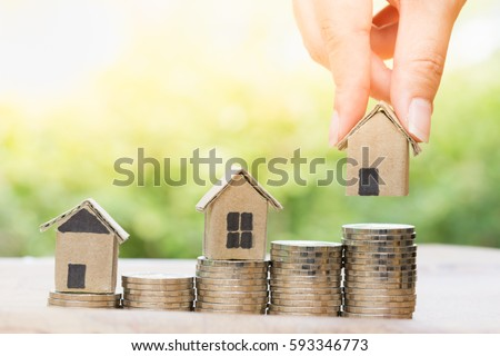 Concept for property ladder, mortgage and real estate investment. Woman's hand putting house model on top of coins stack.