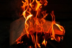 Concept for the destruction of confidential documents.Burning book on fire at night. People don't like reading. Books on fire. Burning news. Burned thoughts of books.