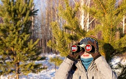Concept for the upcoming new year 2021 and Christmas. Young woman with binoculars and numbers 2021 in eyepieces in the winter forest.