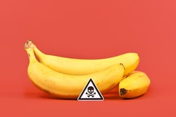 Concept for unhealthy or toxic substances in food like pesticide residues with skull warning sign in front of banana fruits on red background