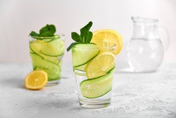 Concept 2 glasses with water and fresh slices of cucumber and lemon with mint on a light concrete background in a high key