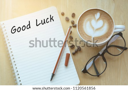 Concept good luck message on notebook with glasses, pencil and coffee cup on wooden table.  Sunlight in the morning. #1120561856