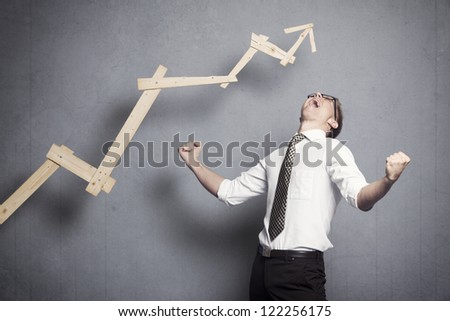 Concept: Great achievement in business. Enthusiastic young businessman cheering in front of business graph with positive trend, isolated on grey background.