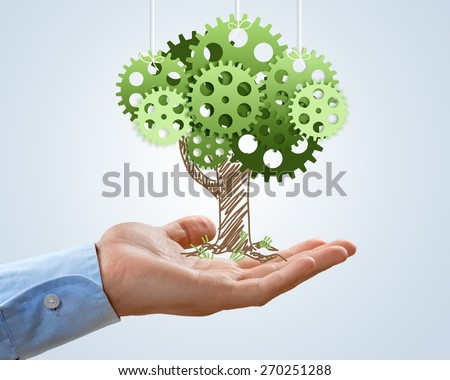 Concept. Hand hold green tree of industrial gear, environmental concept