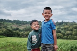 Concept happy asian kids lifestyle. Older brother hugs  younger brother ,by the neck, shoulders with big smile on green mountain background in a countryside Thailand