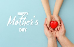 Concept Happy Mother's Day or International Day of Families.Happy women's day.Heart in the hands of daughter and mother on a blue background.I love you.Banner for store.Greeting card. Top view. Banner