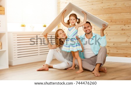 concept housing a young family. Mother father and child in new house with a roof Foto stock ©