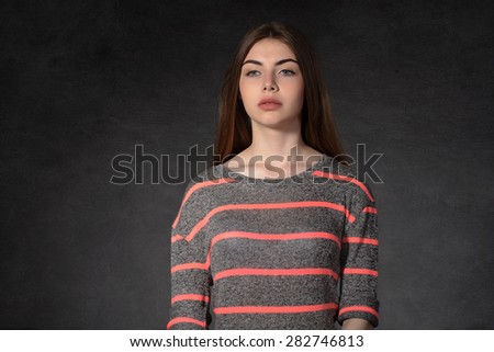Concept human emotions. Girl shows sadness against the dark background