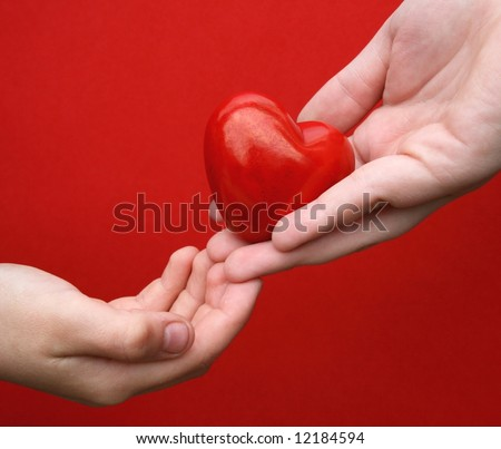 "Concept/ Idea: ""I give you my heart"" .One hand give a heart in another hand in front of red background"