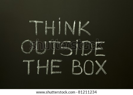 Concept image about unconventional or different thinking. 'Think outside the box' handwritten with white chalk on a blackboard.