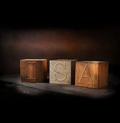 Concept-image for Individual Savings Account called an ISA. Stained and gold wooden blocks with embossed initials of ISA shot against a rustic background with generous accommodation for copy space.