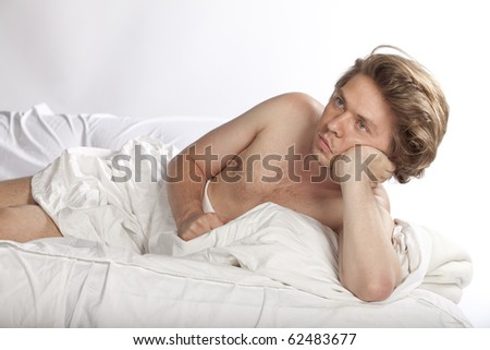 Concept image for insomnia. Lonely young man lying in bed restless. Studio image. See more in my portfolio