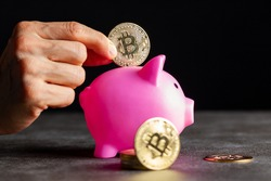 Concept image for using digital crypto currency for savings. A caucasian woman is putting a symbolic bitcoin (BTC) coin into a piggy bank as a saving modality. Isolated image against dark background