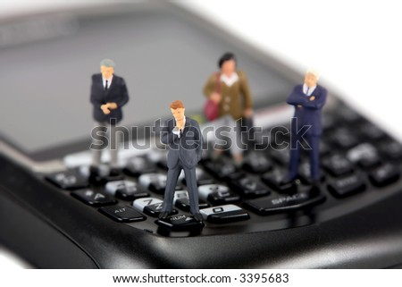 Concept image of a group of miniature businessmen and businesswomen standing on the keys of a cellphone. Focus is on the man in the center.