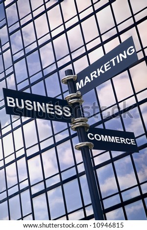 Concept image of a signpost with Business Marketing and Commerce against a modern glass office building with sky reflection.