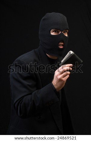 Concept image of a thief wearing a black business suit and holding a wallet, shot against a dark background