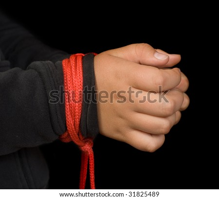 Concept image of child abuse featuring a young girls hands tied with red rope