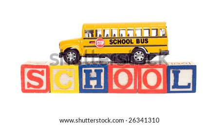 Concept image of education using a toy school bus and baby letter blocks, isolated against a white background