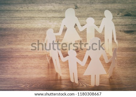 concept image of Family paper chain cutout holding hands, over wooden table #1180308667