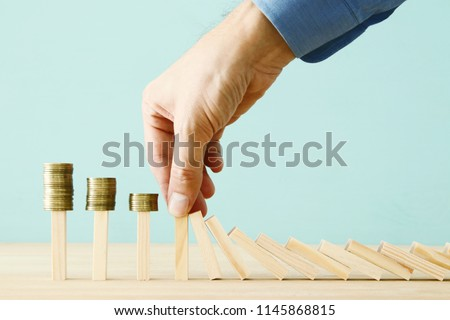 concept image of investing and banking. A businessman stops the domino effect from risking financial investment #1145868815