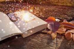 concept image of magic flowing and sparkling from bookmark of book laying on wooden log