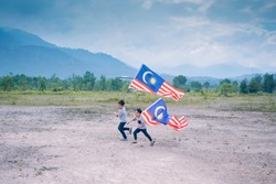 Concept image of Malaysian Independence Day. Two boy holding Malaysian flag happily with nice Banjaran Titiwangsa view in the background.