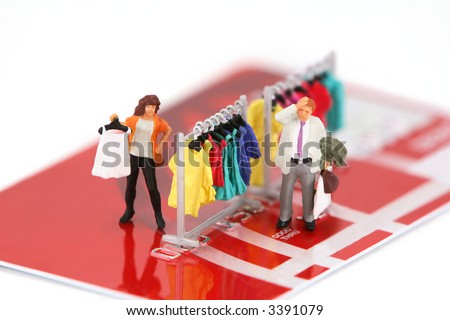 Concept image of miniature shoppers on a credit card. The woman is shopping for clothes while her husbands is stressing how much this is going to cost him.