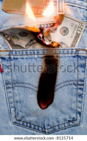 Concept image of money burning a hole in a jeans pocket