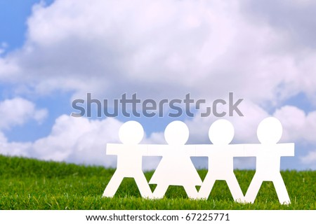 Concept image of paper people holding hands in a field with a blue sky background.