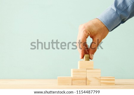 concept image of Saving money or investing. putting stack of coins at the top #1154487799