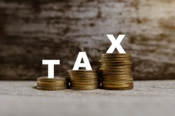 Concept image of TAX containing increasing coin value with wording over beautiful wooden background