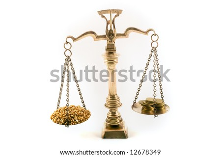 concept image of wheat grains and coins on scales to illustrate the value of food