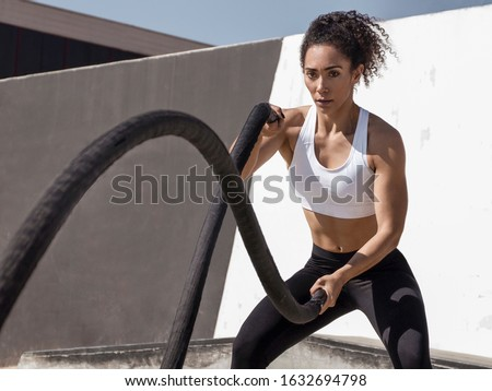 Concept image - Powerful fitness woman training with black battle ropes crossfit at outdoor, with white top