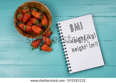 Concept image, strawberry with notebook on a blue wooden background with words Body Mass Index. Health concept.