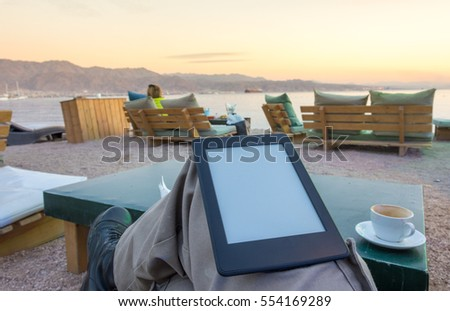 Photo of Concept image with room to paste text: enjoying an e-book / e-reader and a cup of afternoon cappuccino coffee on beach