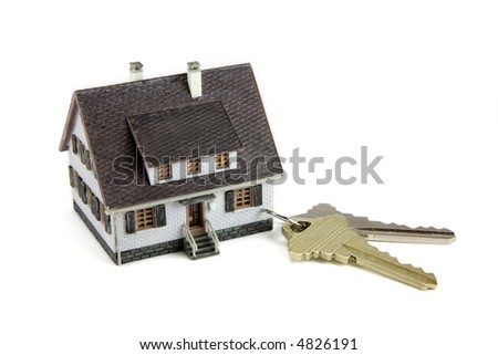 Concept images of a miniature house connected to a key chain with house keys. White background.
