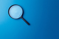Concept information search. Magnifying glass on classic blue background. Top view. Flat lay. Copy space. Minimal creative concept. Trendy color. Searching information data on internet