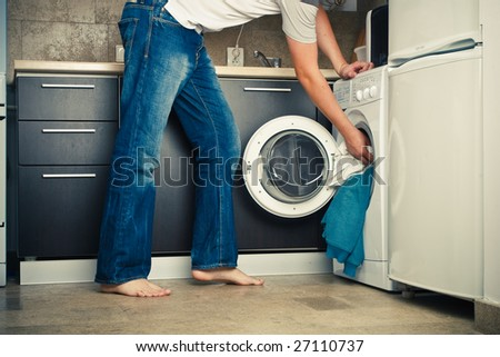 Concept Man putting his laundry into the washing machine - stock photo