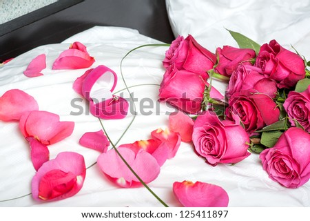 Concept. marriage proposal - roses and a diamond ring on a pillow in bed